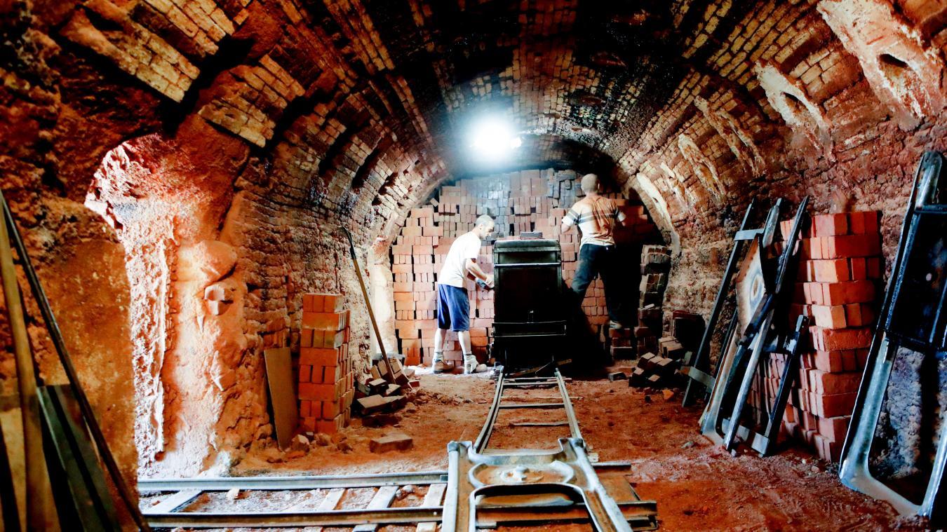 Omar et Dominique s'occupent de défourner les briques cuites. Derrière eux, à quelques mètres, Jean-Louis et Philippe chargent la prochaine fournée. PHOTO SAMI BELLOUMI