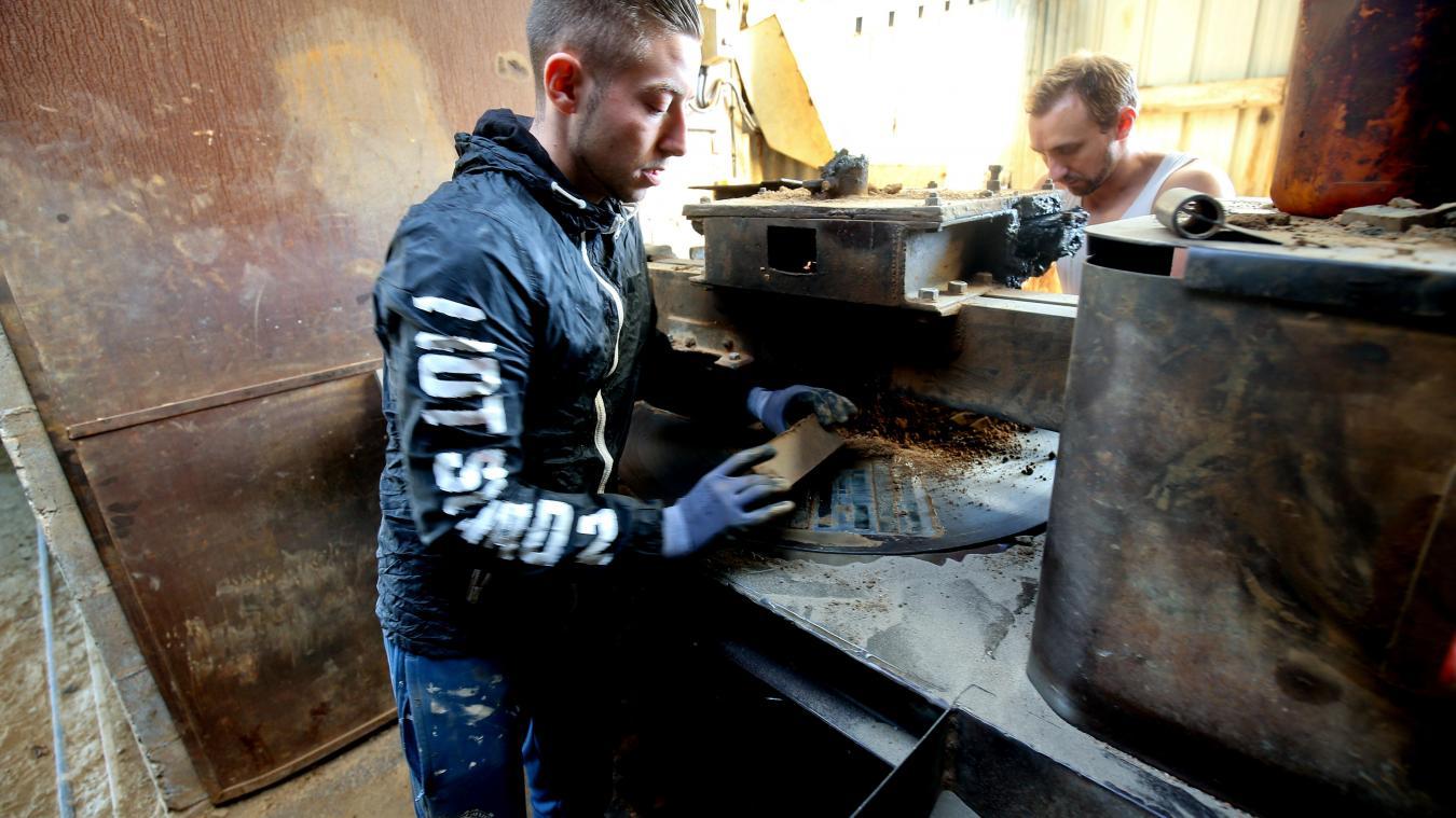 Sébastien et Steven récupèrent les plaquettes, en sortie de presse. Elles sont ensuite cuites dans un four à gaz, contrairement aux briques. PHOTO SAMI BELLOUMI